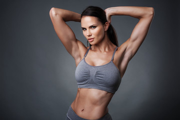 studio photo of posing sexy woman with nice fitness body isolated over gray background