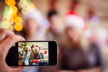 Taking picture of friends at Christmas eve with smart phone.