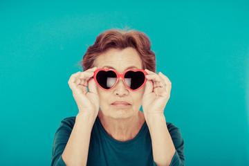 サングラスをかけているシニア女性 青背景