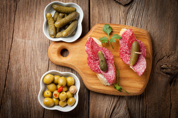 Tapas with sliced salami, olives and cucumber on a wooden table.