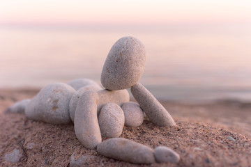 Figurine of pebbles on seashore