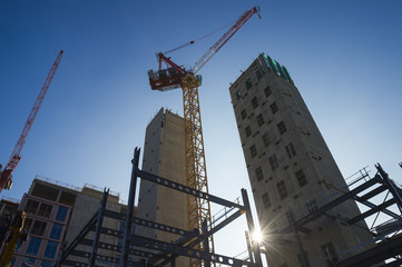 Modern hi-rise towers construction site with cranes backlit by morning sun under bright blue sky