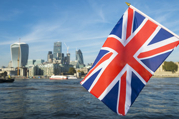 Union Jack flag flying over the London skyline of the financial City center at the River Thames