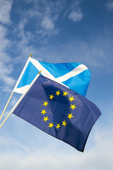 Scottish and EU flags flying in bright blue sky