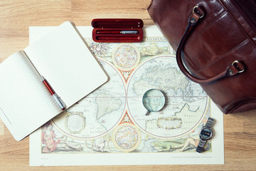 Packed Suitcase of Retro Vacation Items - Old Map, Bag, Magnifier, Watch, Pens, Opened Notebook, Top View