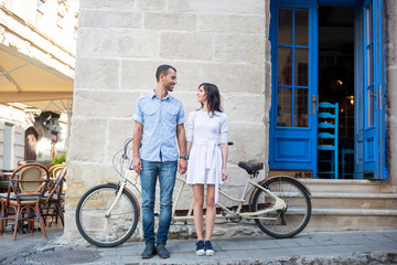 Guy and girl stand holding hands and looking at each other on the background of their tandem bike, walls and vintage door on the sidewalk of a city street. Lviv, Ukraine