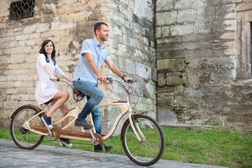 Smiling couple riding on retro tandem bicycle against the background of the old brick building. Man looks forward and the girl in a white dress looking at the camera. Lviv, Ukraine