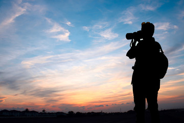 Photographer shooting sunset sky