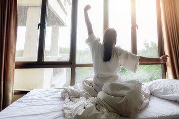 Woman stretching in bed after wake up. Soft light and soft focus to feeling relax and comfortable.