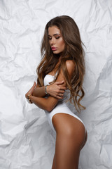Sexy, hot and seductive girl in white seamless body underwear with slim athletic tanned figure is posing in the studio, light background