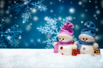 Snowmen dolls on blue winter background