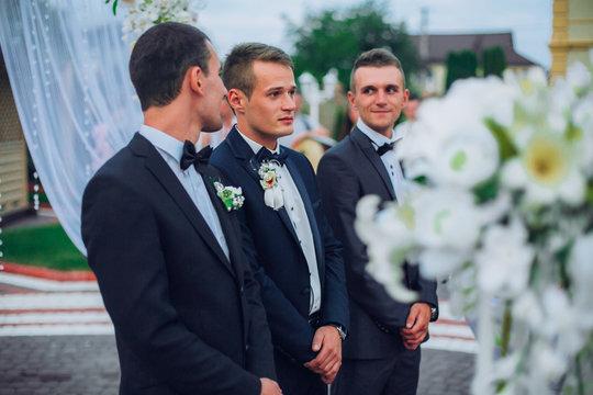 Groomsmen standing on the wedding ceremony outdoors