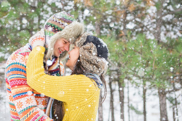 Couple in love walking in the winter woods. Pine Forest, spruce trees. Happy man and a woman. People dressed in sweaters and hats. Emotional people. Snowfall.