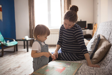 young pregnant mother and son reading a book, lifestyle,