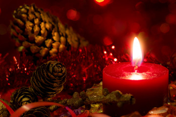 Fototapeta Christmas and New Year`s festive evening burning candle bokeh image. Greeting card dark Background concept with holiday tinsel, fir cones, tree branch and copyspace place for text or logo. obraz