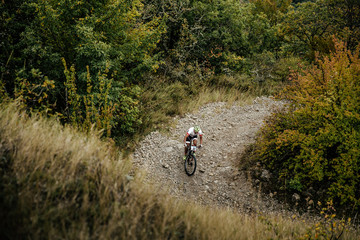 cyclist on sport bike rides on serpentine mountain road. competitions on mountainbike