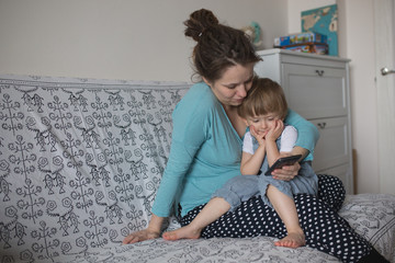 Pregnant mom and son Toddler playing with  phone, lifestyle. Rea