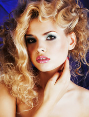 young blonde woman with glamour makeup and hairstyle waves close