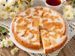 Delicious apple pie and chrysanthemums on old blackboard