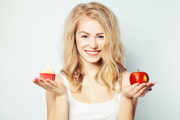 Smiling Woman with Healthy and Unhealthy Food. Difficult choice.