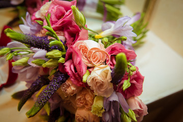 Two gold wedding rings lie on a bouquet.
