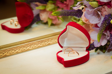 Bridal bouquet and two wedding rings in red box in the shape of a heart.