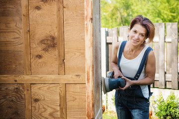 Happy mature woman is polishing old furniture outdoors
