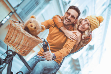 Happy young couple going for a bike ride