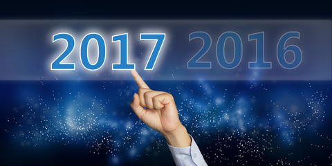 Photo image of male hand clicking New Year 2017 numbers on virtual cyber space