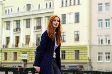 Young red woman walking in the city