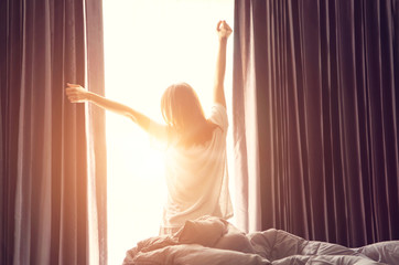 Woman standing near the window while stretching near bed after waking up with sunrise at morning, back view