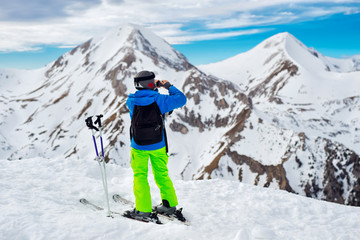 Skier making panorama shot of the mountains full of snow.
