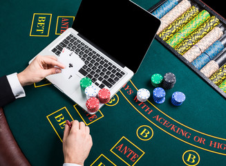 casino, online gambling, technology and people concept - close up of poker player with playing cards