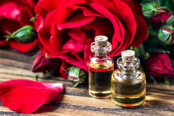 Essential oil in glass bottle with red rose flowers and petals on wooden background. Beauty treatment. Spa and aromatherapy concept. Selective focus