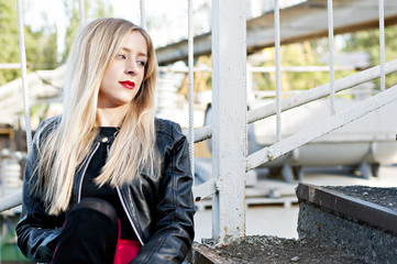 Woman blonde in a red skirt black jacket on the stairs