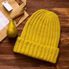 Warm soft yellow hat made by hand on a dark Board next with pears and cinnamon sticks