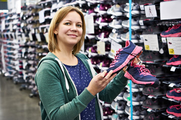 Woman chooses running shoes in store