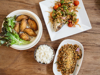 Thai food (fried salted fish topped with herb, fried chicken wings, spicy minced pork) and cooked rice on wooden table