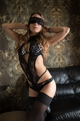 Brunette sexy woman in black lingerie with blindfold