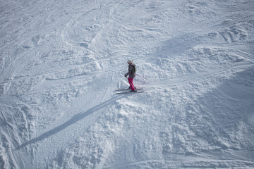 Young girl in colorful outfit skiing downhill on mountain.