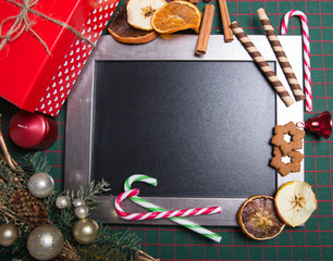 Chalkboard decorated with Christmas decorations like gingerbread cookies, candies and baubles.