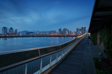 View of a residential district along the Han River and wooden boardwalk at the Mapo Bridge in Seoul, South Korea, in the evening. Copy space.