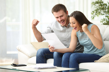 Excited couple reading a letter at home
