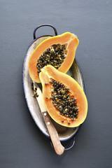 Sliced fresh papaya fruit on an enamel plate