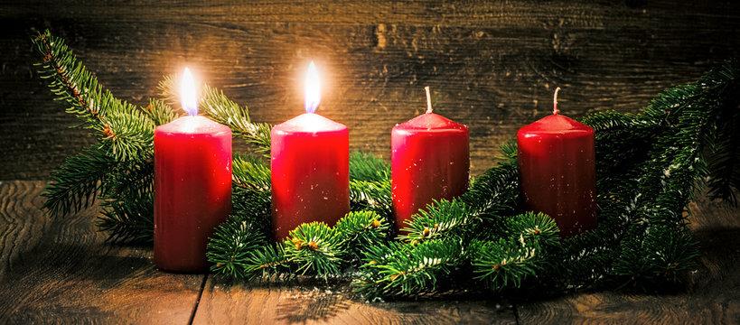 Zweiter Advent: zwei leuchtende Kerzen vor einem Holzhintergund