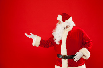 Santa Claus pointing in blank a place, red background