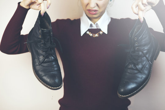 woman holding up men's smelly shoes