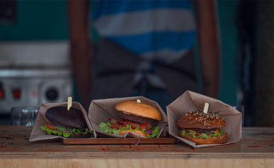 Three Different Burgers Laying On Wooden Counter