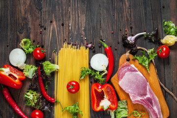 Italian food background, with meat, tomatoes, spaghetti, garlic, peppercorns, chili pepper on wood table