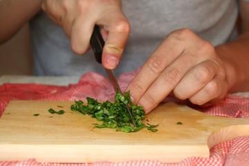 Unrecognizable man cutting parsley. Selective focus.